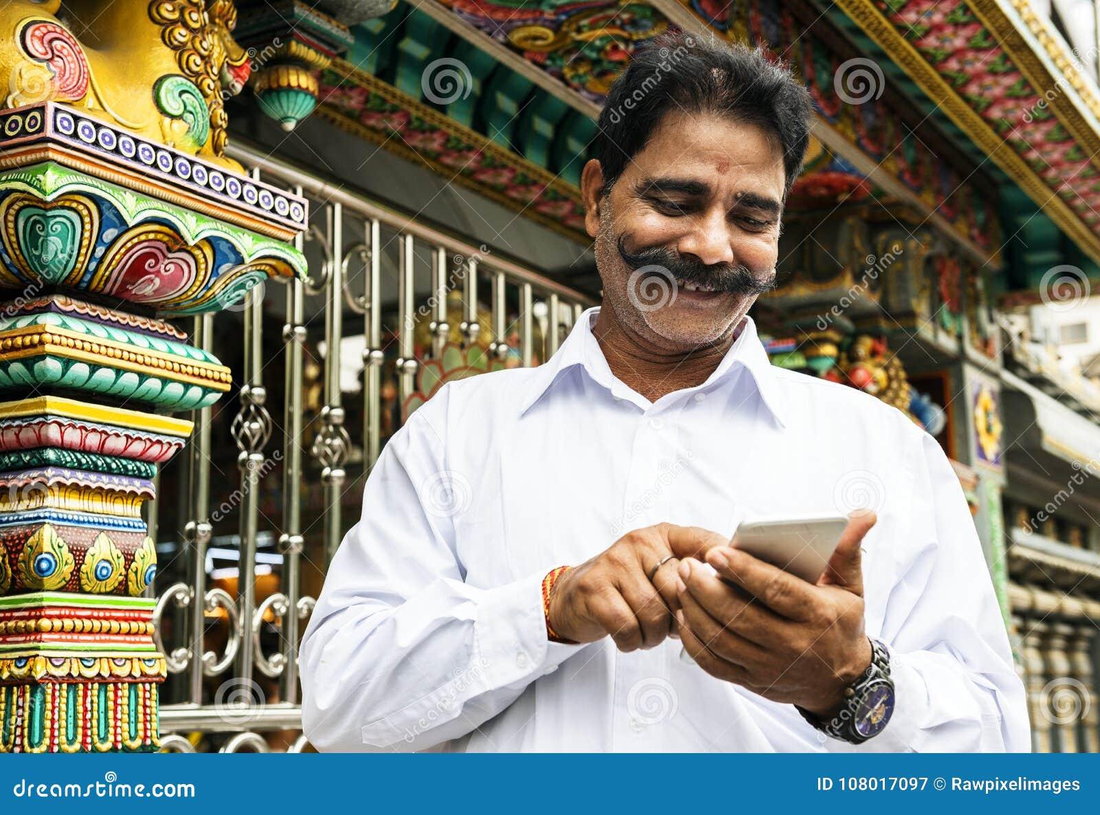 Hombre indio que usa el teléfono móvil