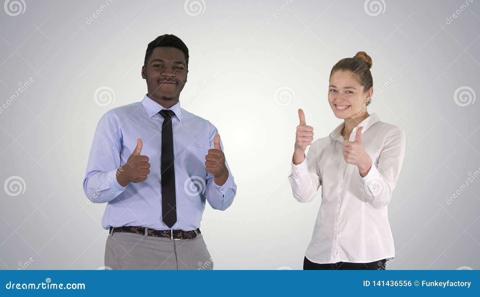 Hombre internacional y mujer sonrientes felices que muestran los pulgares para arriba en fondo de la pendiente