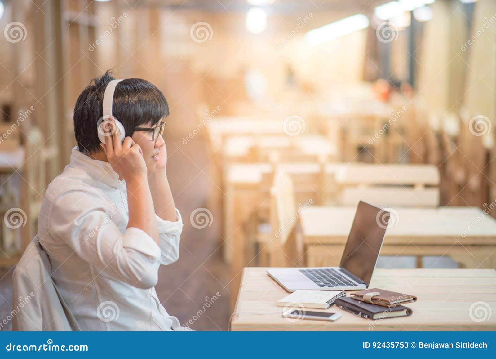 Hombre joven asiático con los auriculares que escucha la música