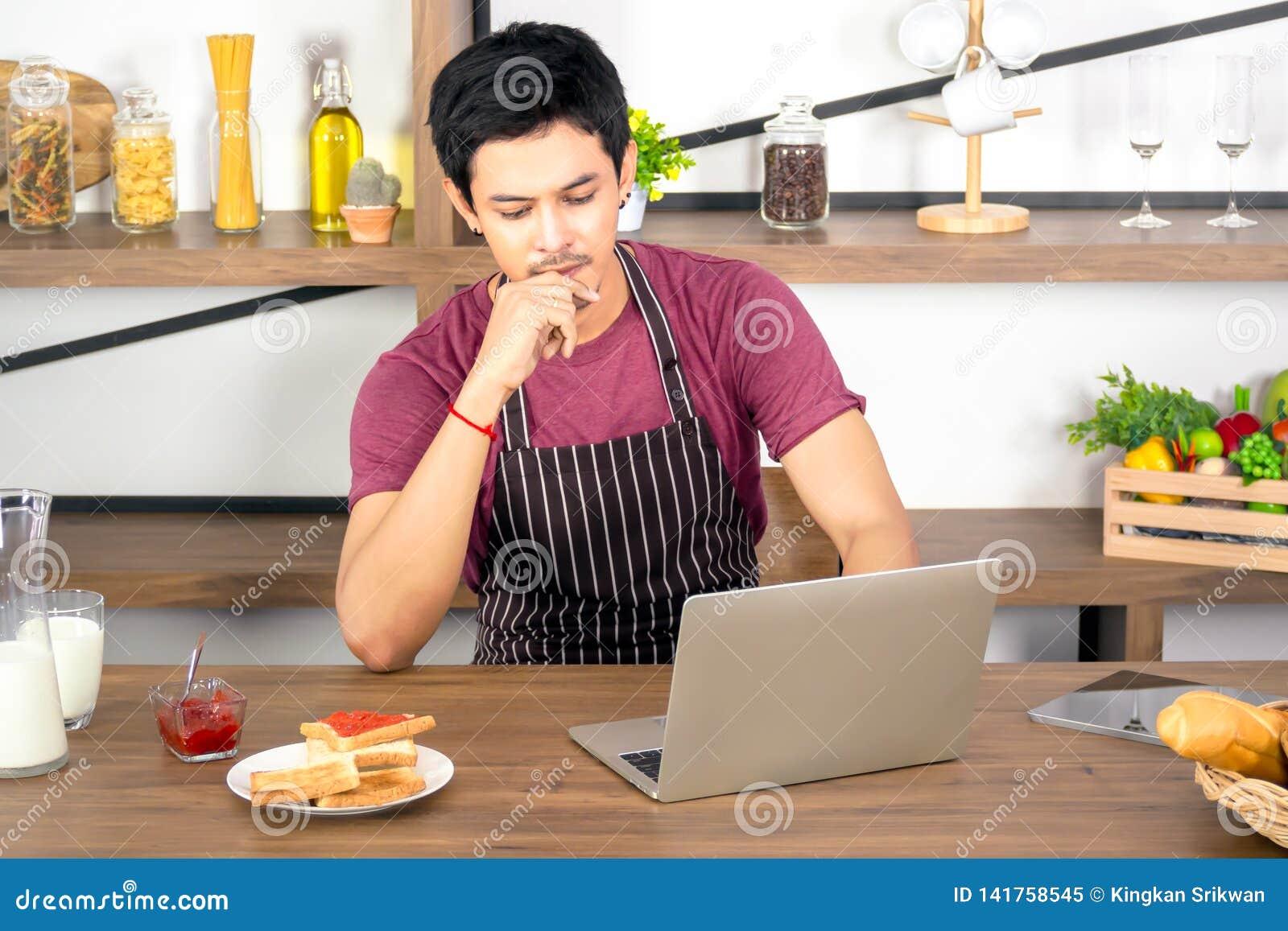 Hombre joven asiático usando el ordenador portátil para el funcionamiento en línea