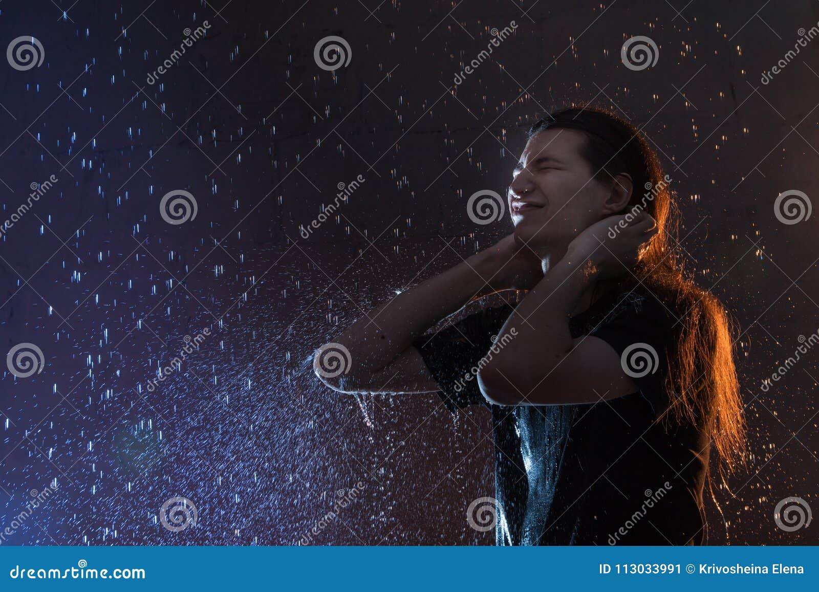 Hombre joven atractivo en ropa mojada negra debajo de la lluvia y del chapoteo del agua, foto del estudio