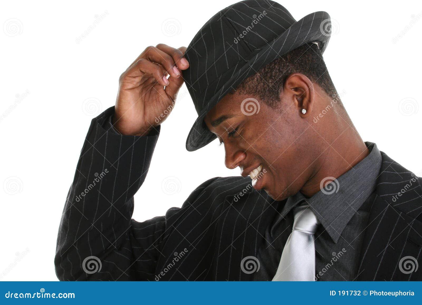 Hombre joven atractivo que inclina su sombrero