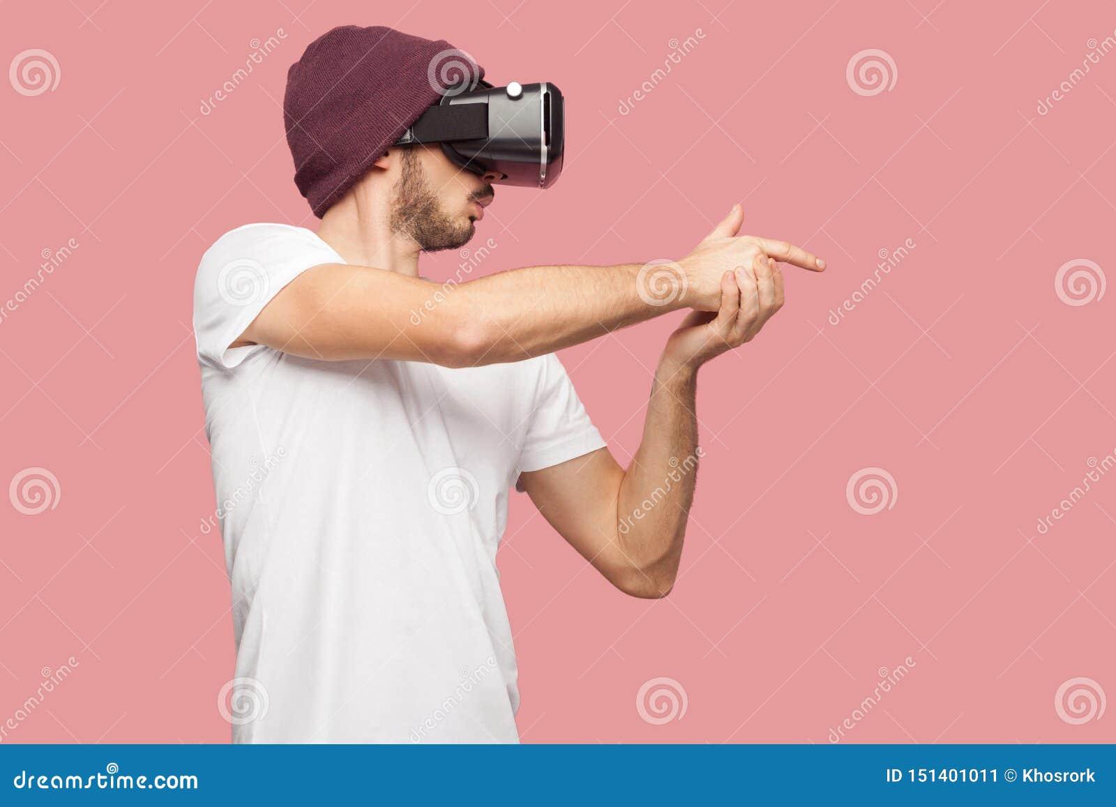 Hombre joven barbudo confiado del inconformista en la camisa blanca y la situación casual del sombrero, vr que lleva que juega al