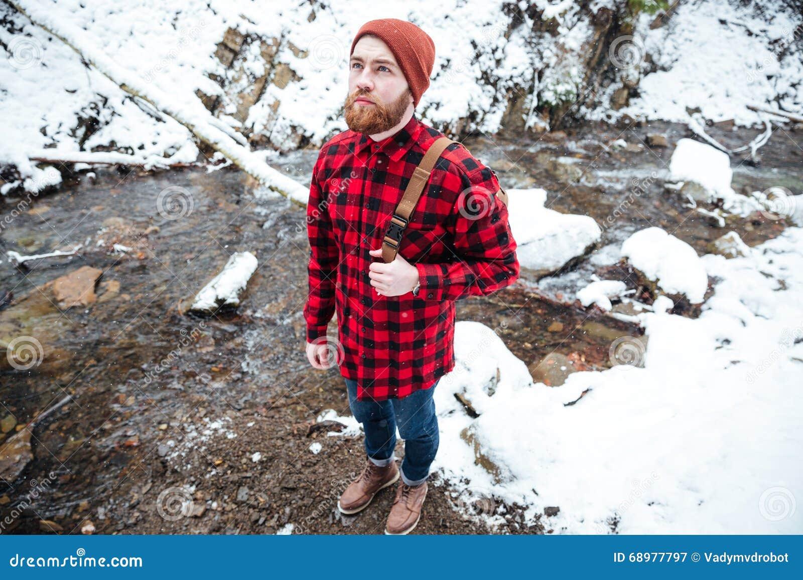 Hombre joven barbudo pensativo que coloca el río cercano de la montaña en invierno