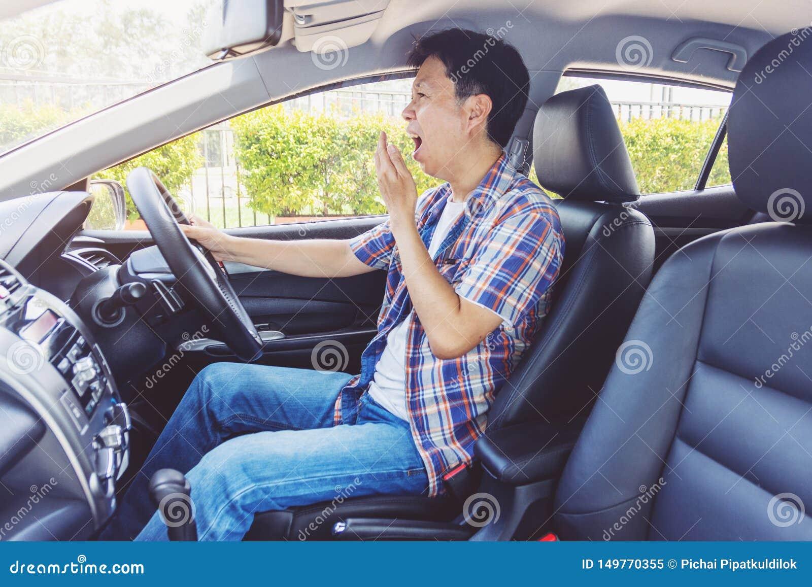 Hombre joven cansado de Asia que conduce su coche