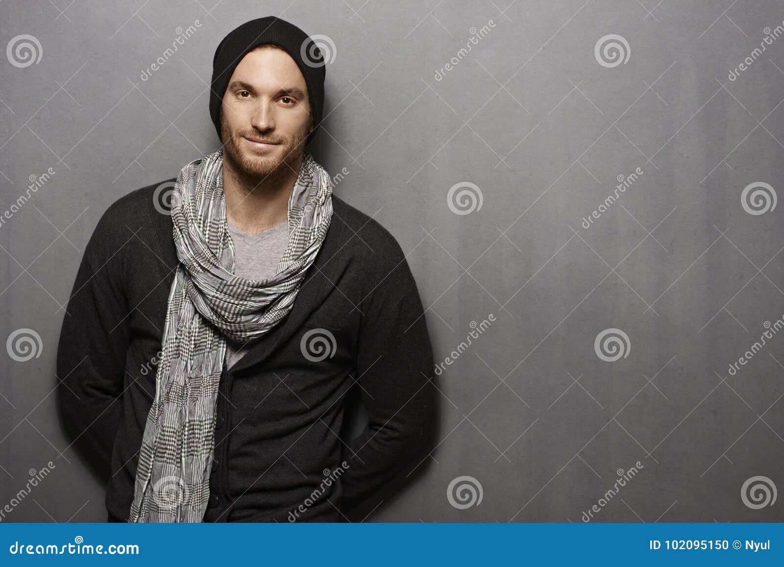 Hombre joven casual que sonríe sobre la pared gris