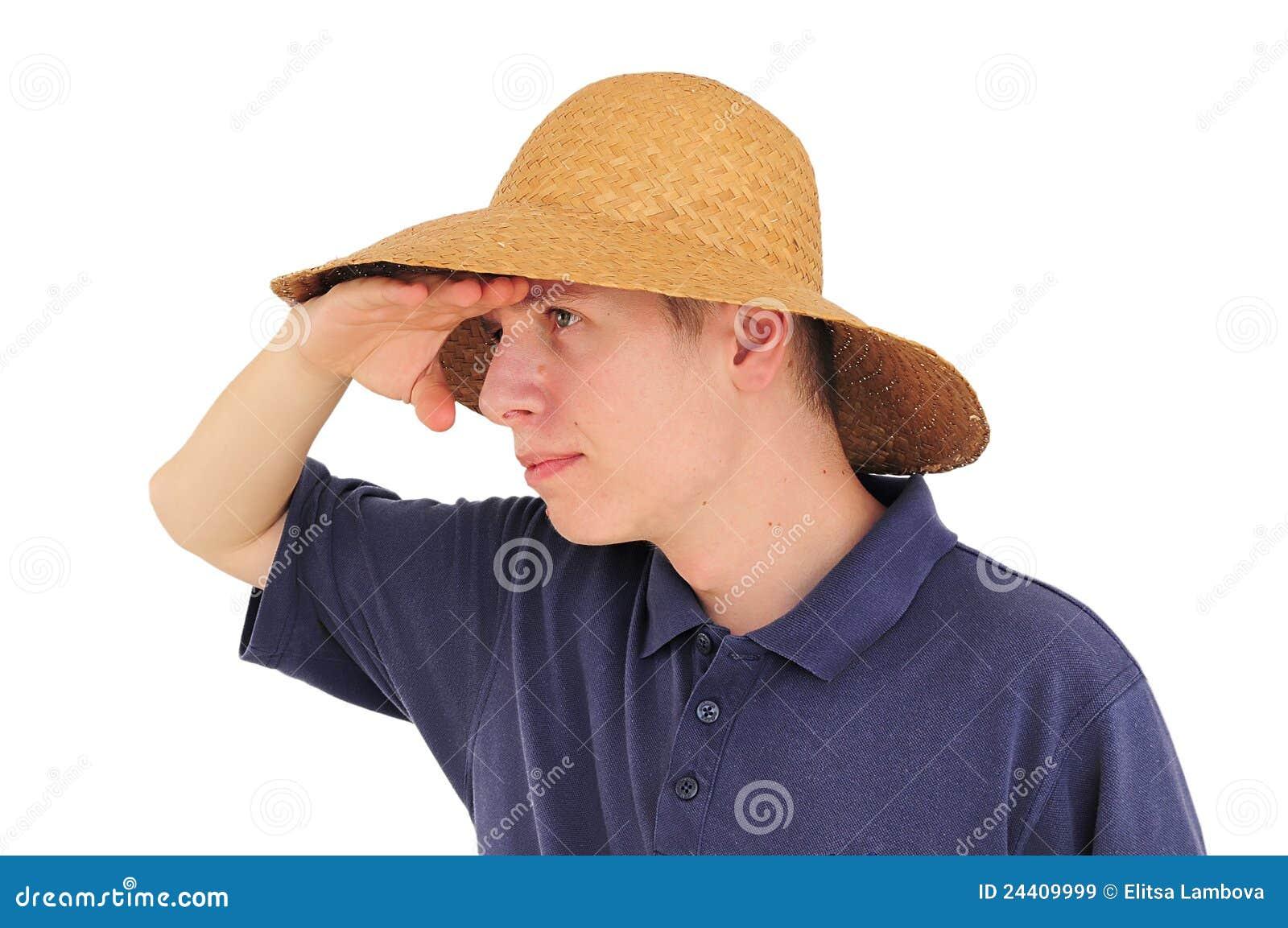 Hombre joven con el sombrero de paja que mira en la distancia