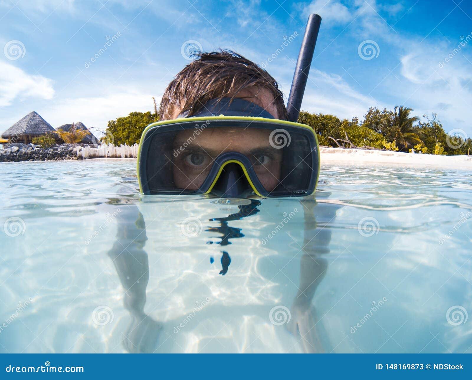 Hombre joven con la máscara del equipo de submarinismo en el agua azul clara que mira a la cámara