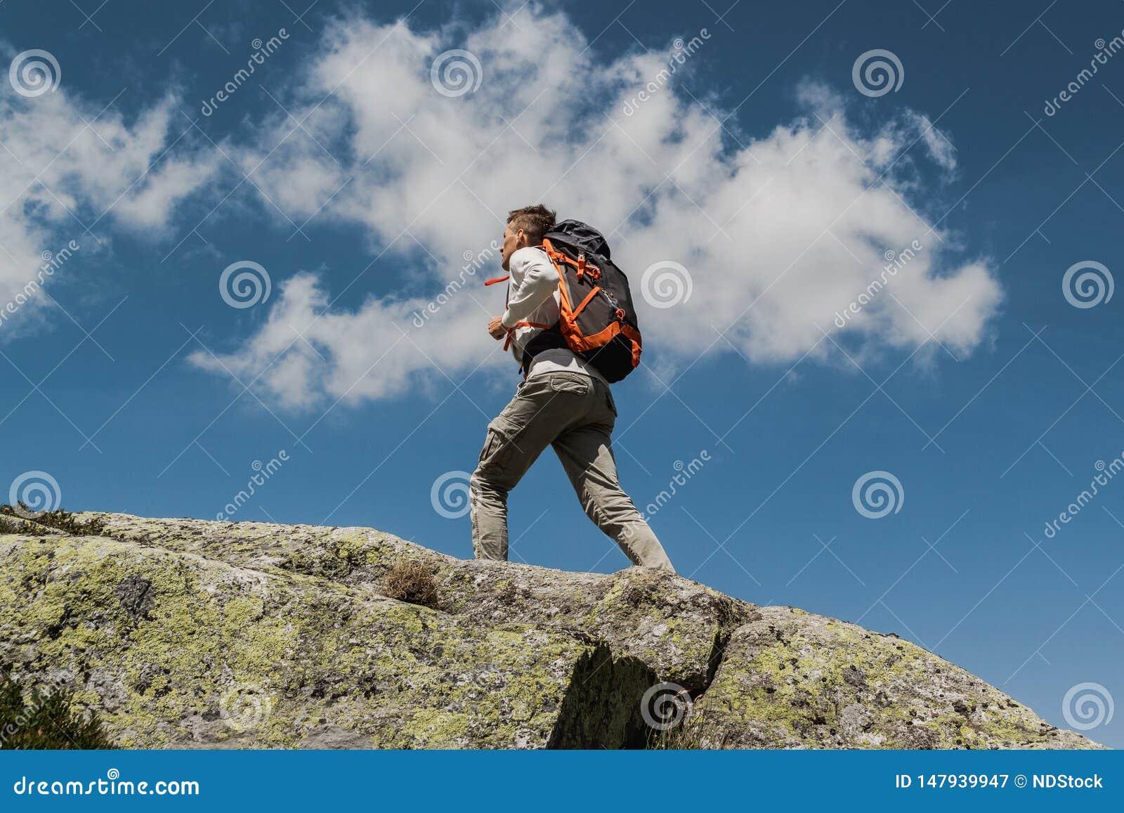 Hombre joven con la mochila grande que camina para alcanzar el top de la montaña durante un día soleado