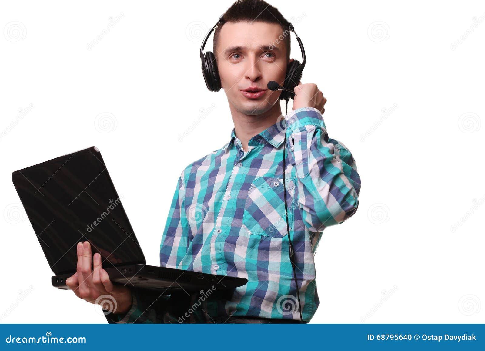 Hombre joven con las auriculares que sostienen el ordenador portátil - hombre del centro de atención telefónica con hea