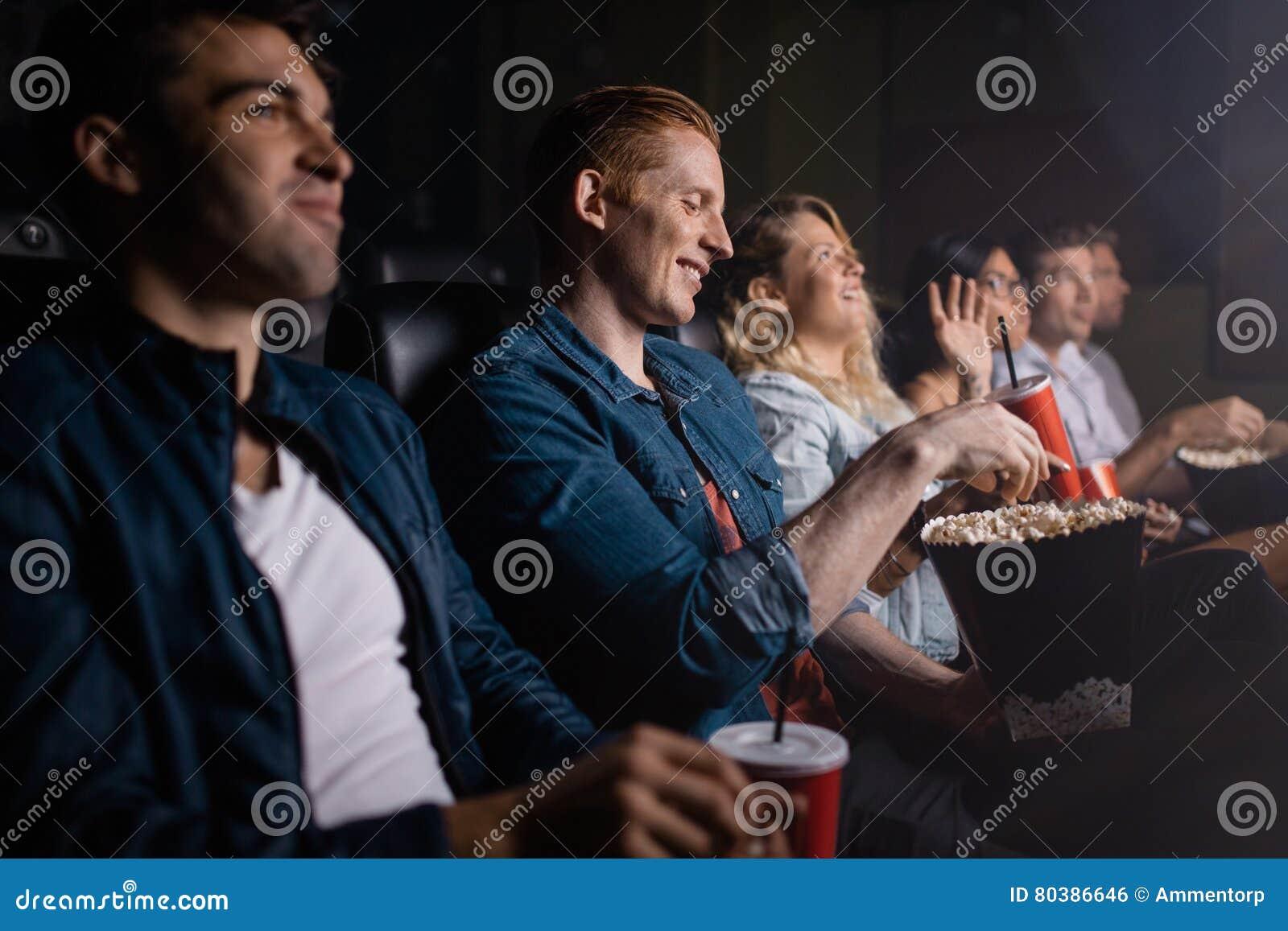 Hombre joven con los amigos que miran película en cine