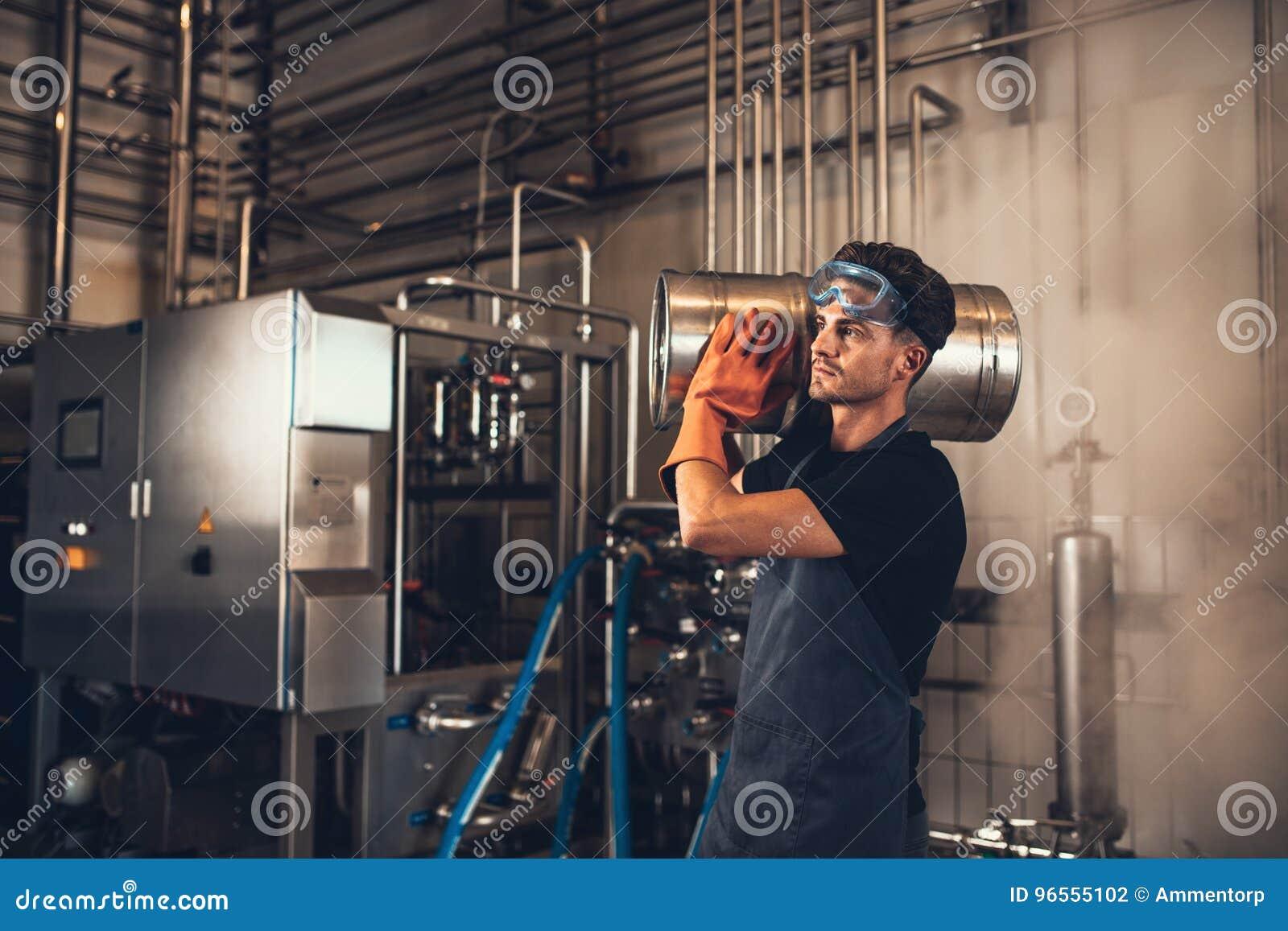 Hombre joven con los barriles de cerveza del metal en la cervecería