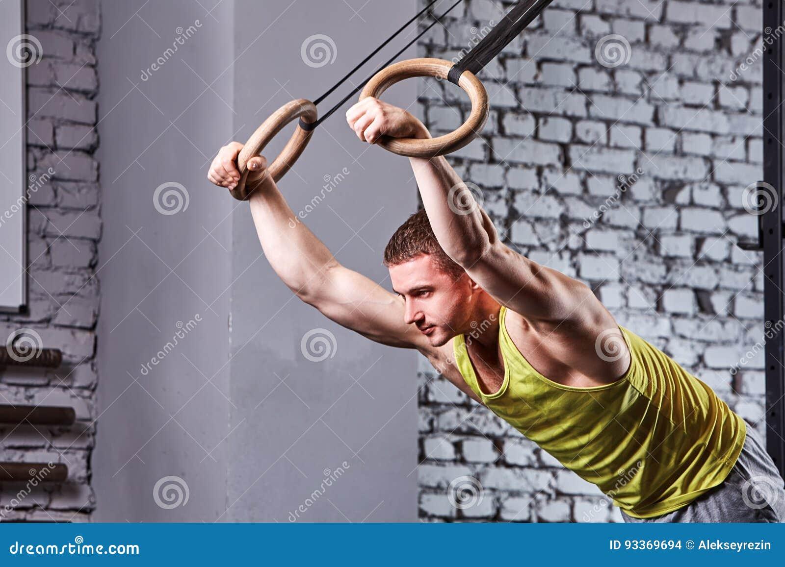 Hombre joven del atleta en el sportwear que levanta en los anillos gimnásticos contra la pared de ladrillo en el gimnasio apto de