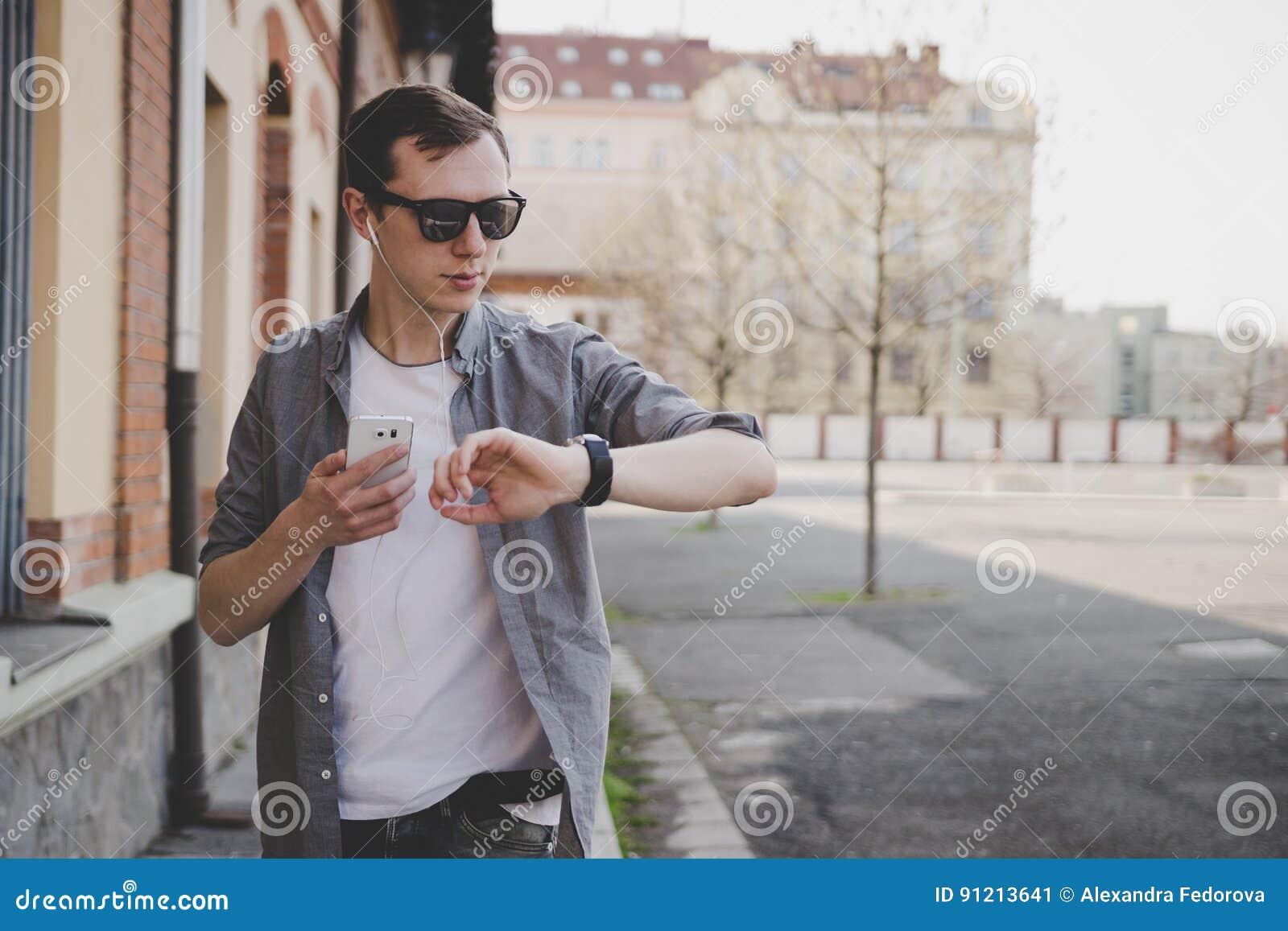 Hombre joven del inconformista que camina en la calle, mirando el reloj y usando su smartphone Con el espacio de la copia