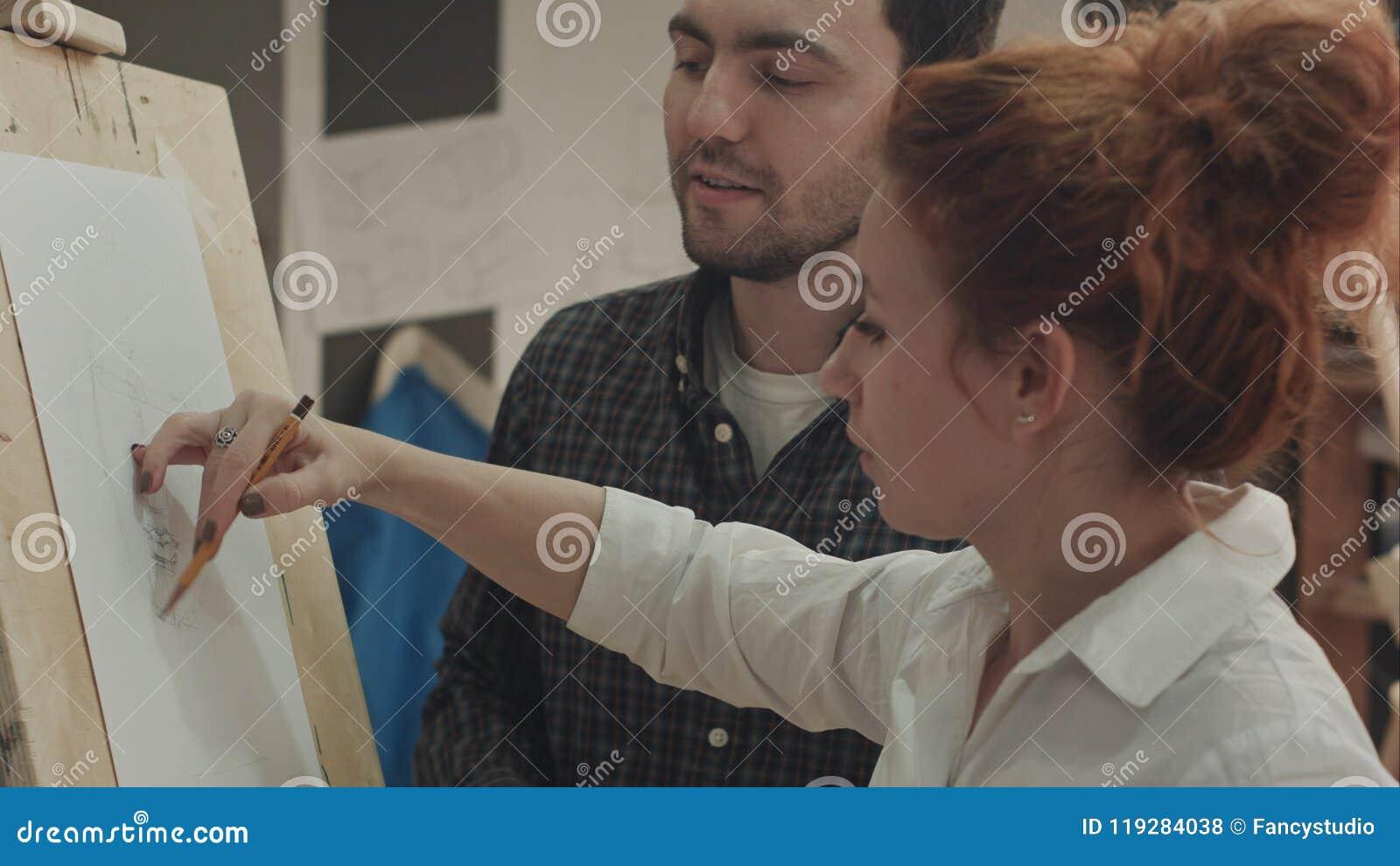 Hombre joven del pintor de la mujer enseñando a cómo dibujar la cara