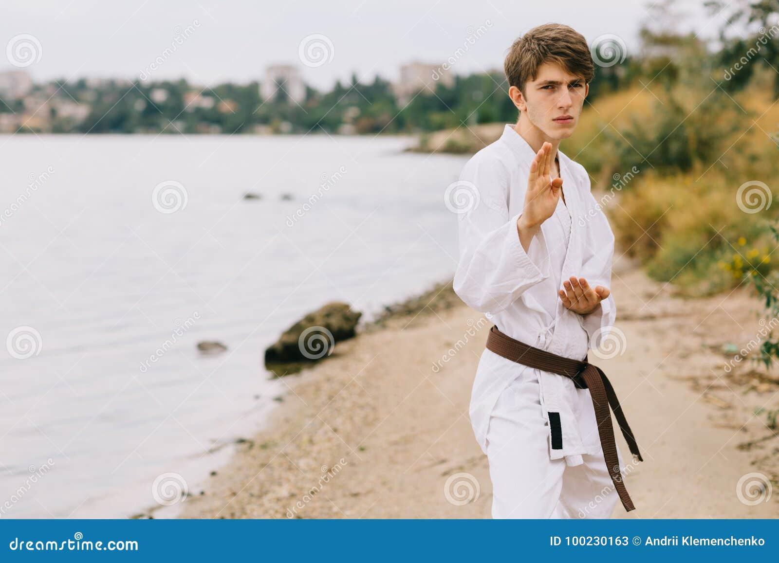 Hombre joven deportivo en el entrenamiento del karate del aire libre Muchacho en kimono en un fondo natural Ejercicio de concepto