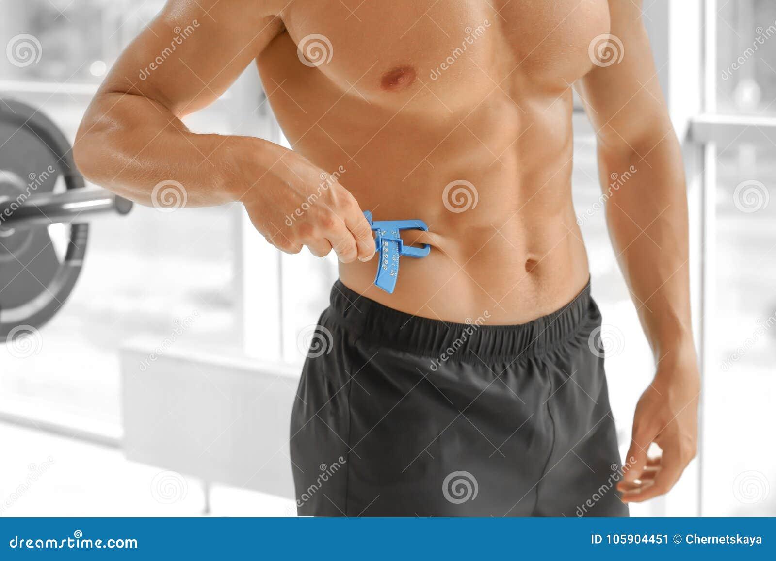 Hombre joven deportivo que usa el calibrador de las grasas de cuerpo