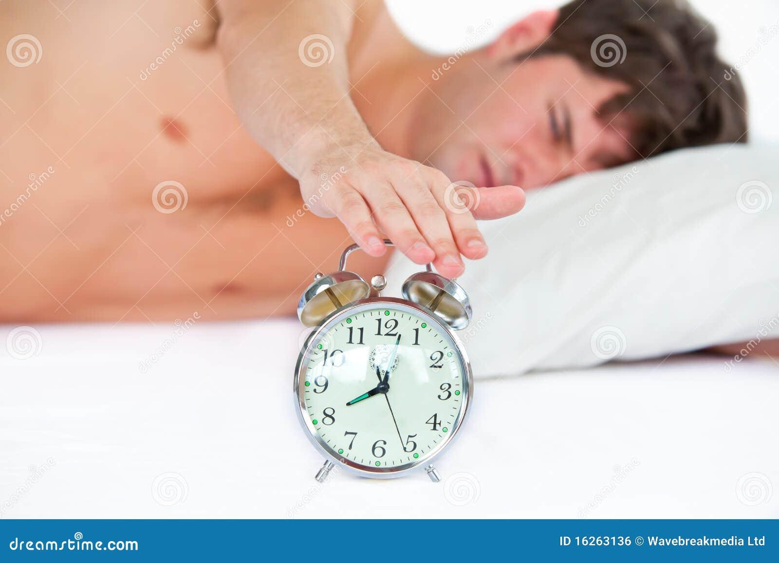 Hombre joven dormido que para su reloj de alarma de sonido for Sonido de alarma