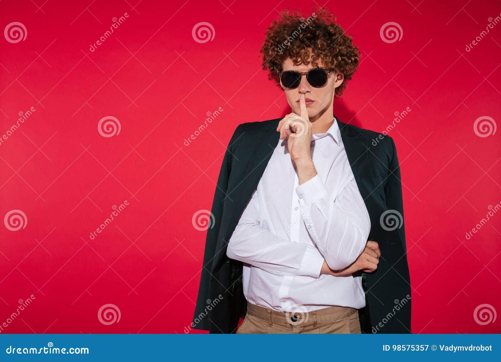 75355cb8f El hombre joven elegante encantador en gafas de sol y la camisa blanca que  muestra silencio gesticulan con el finger sobre los labios aislados sobre  fondo ...