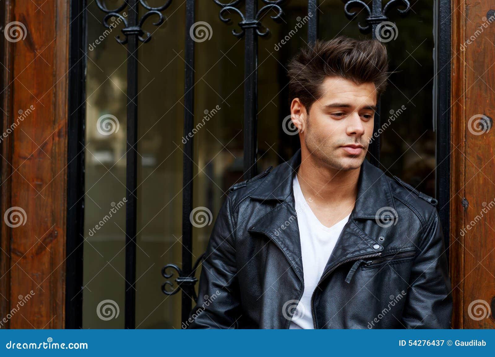 Hombre joven Elegante-vestido que se opone en la calle a puerta de madera