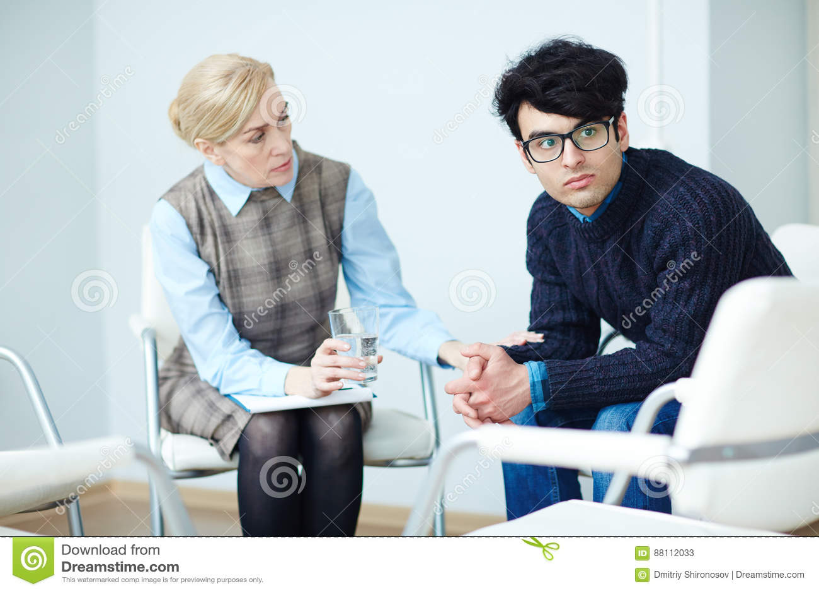 Hombre joven en el asesoramiento de la sesión con el psicólogo
