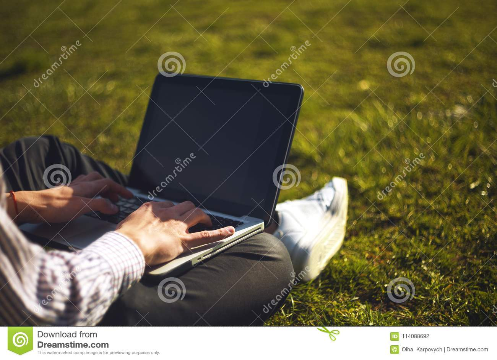 Hombre joven en el parque que se sienta en la hierba con un ordenador portátil Hombre ordenador portátil que usa y que mecanograf