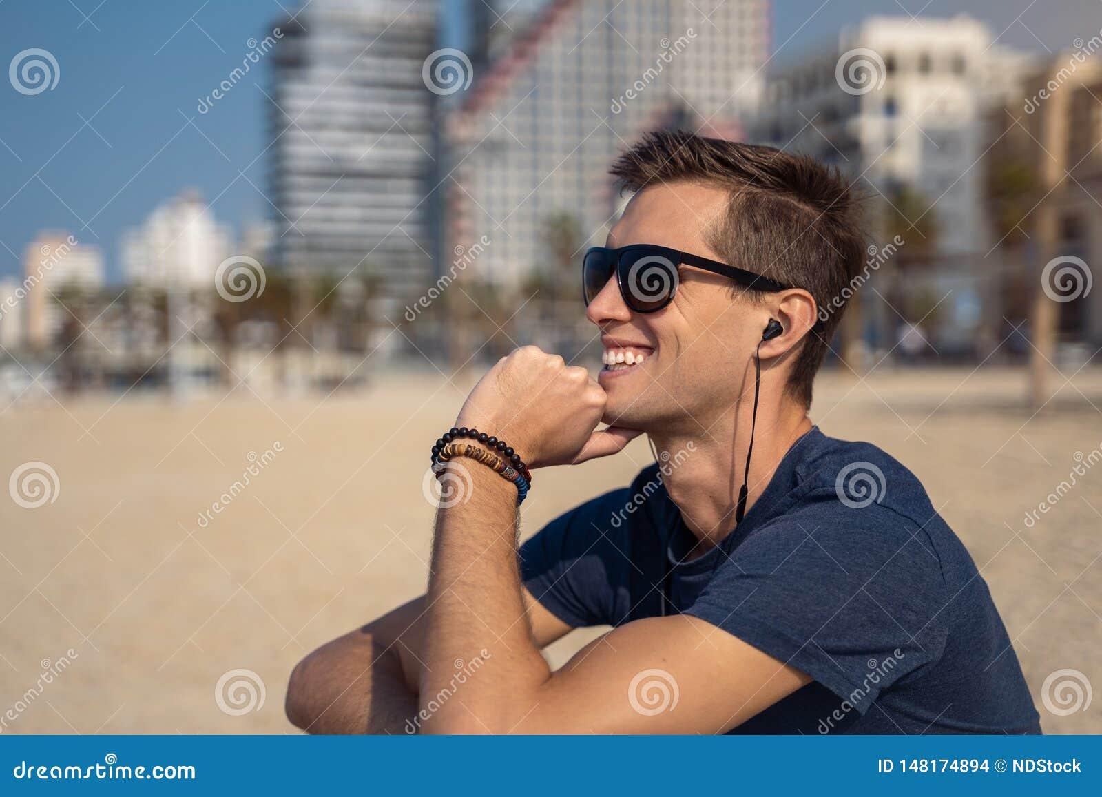 Hombre joven en la m?sica que escucha de la playa con los auriculares horizonte de la ciudad como fondo