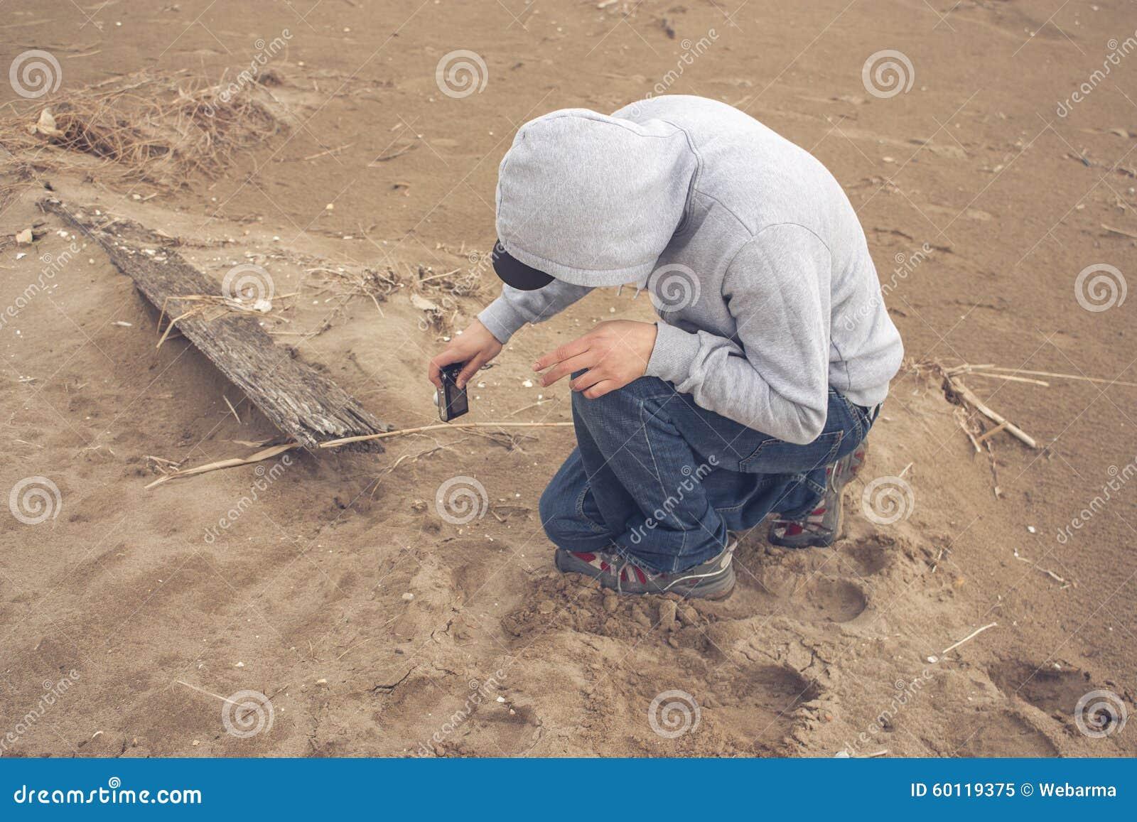 Hombre joven barbudo en la playa en el día nublado que lleva una sudadera  con capucha y una gorra de béisbol 7ba69ce3072