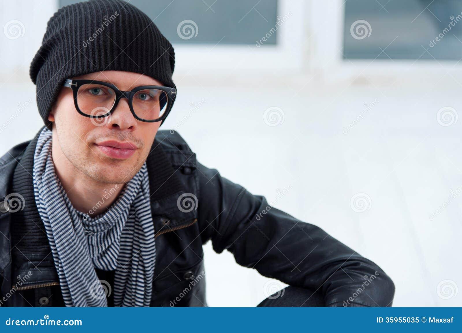 Hombre joven en la ropa casual que se sienta en el piso