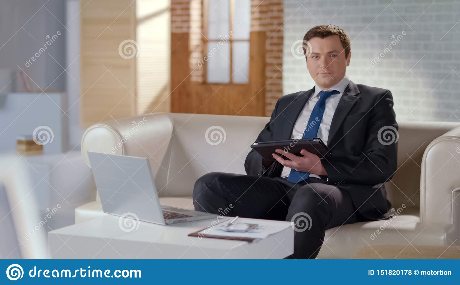 Hombre joven en traje usando la tableta en la oficina, tecnologías modernas para manejar negocio