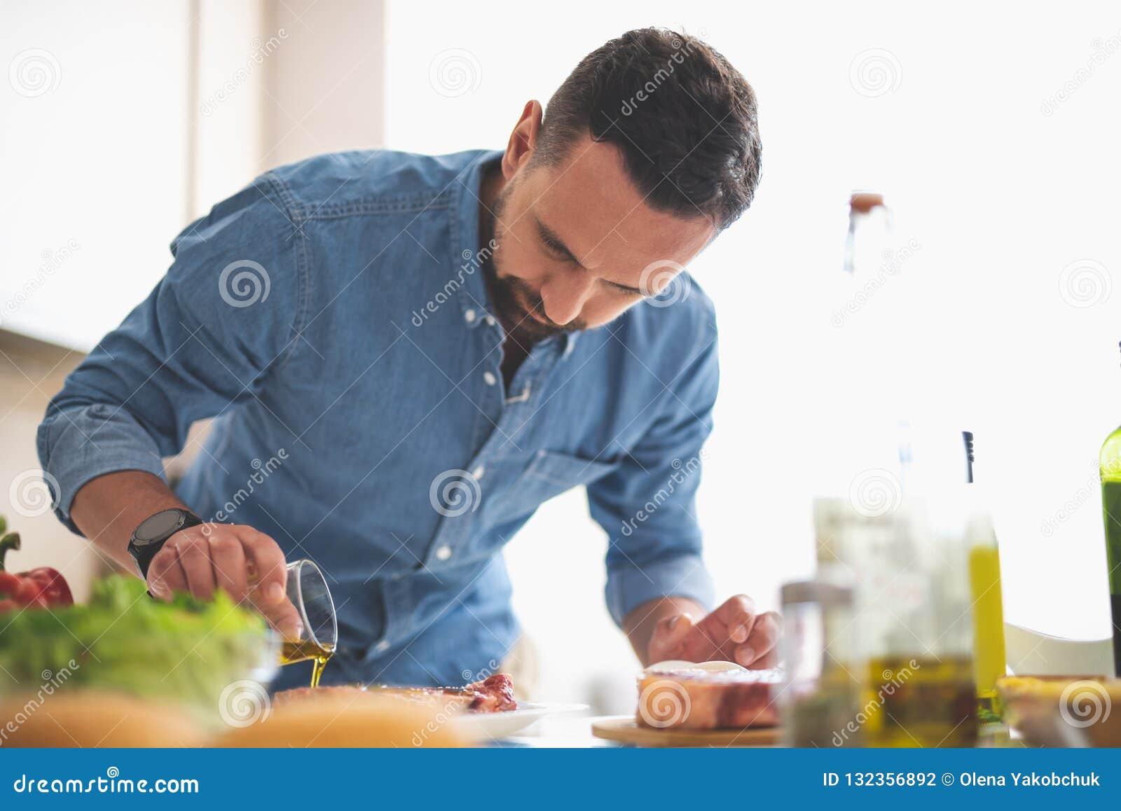 Hombre joven enfocado que cocina la carne mientras que se coloca cerca de la tabla de cocina