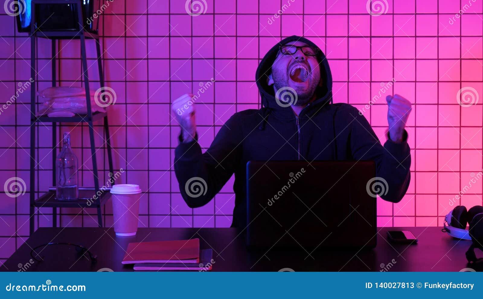 Hombre joven feliz en lentes que mira el juego de ordenador Reacción emocional