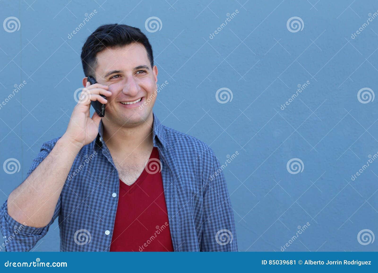 c0f49a4ba Hombre joven feliz que habla en el teléfono celular aislado en fondo azul