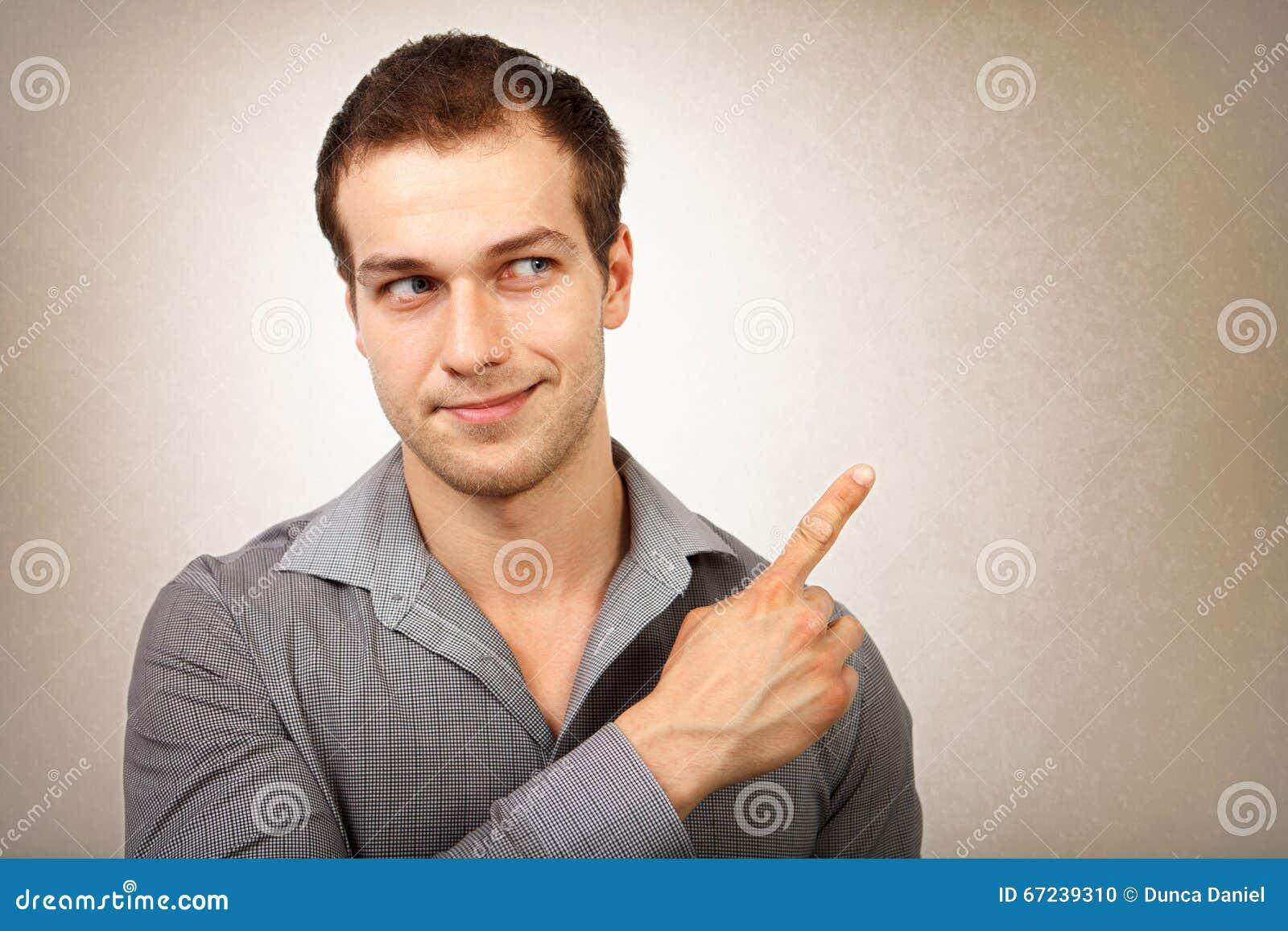 Hombre joven feliz que señala el dedo