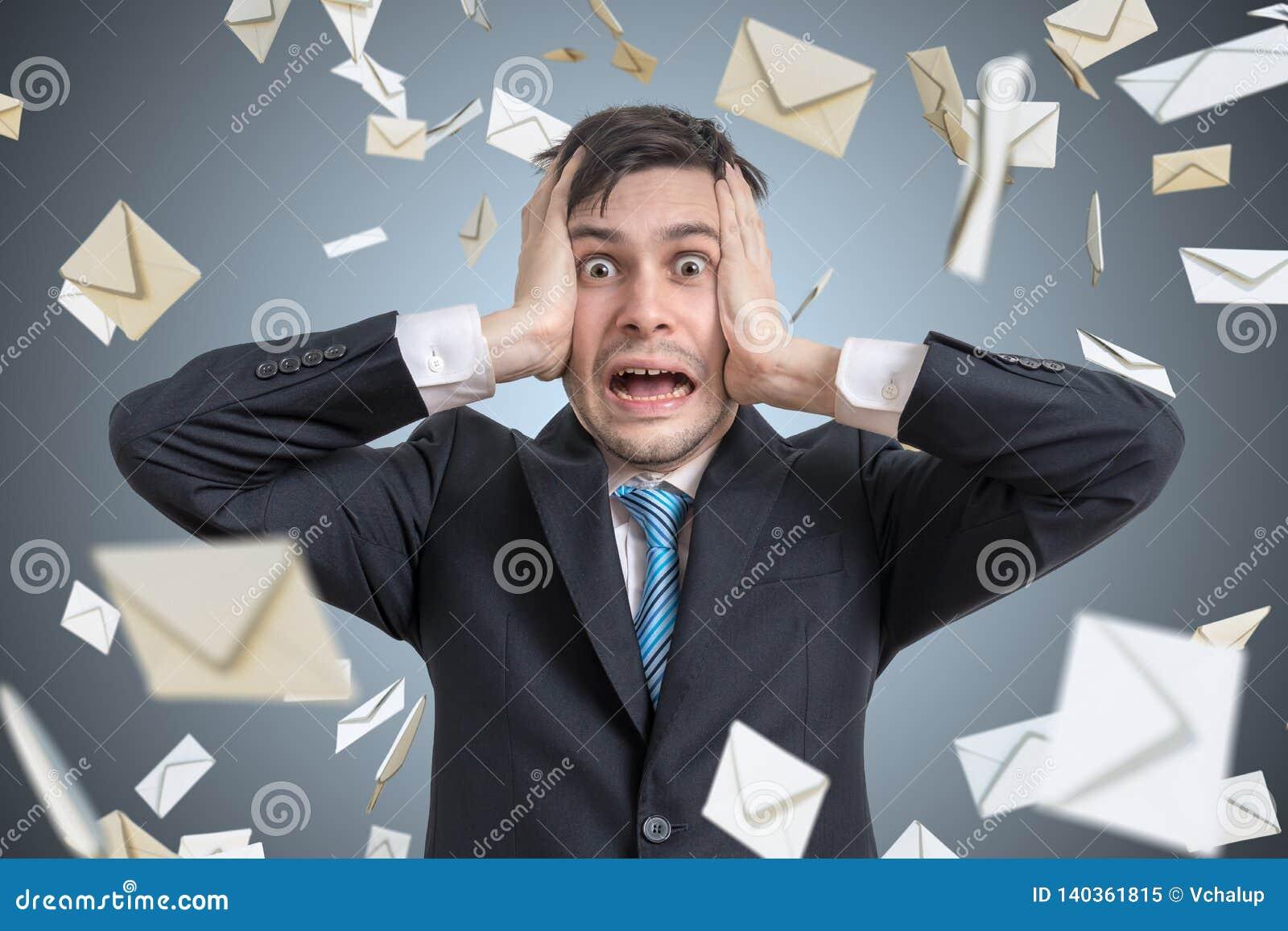 Hombre joven frustrado y muchos sobres que caen Muchos email y concepto del Spam