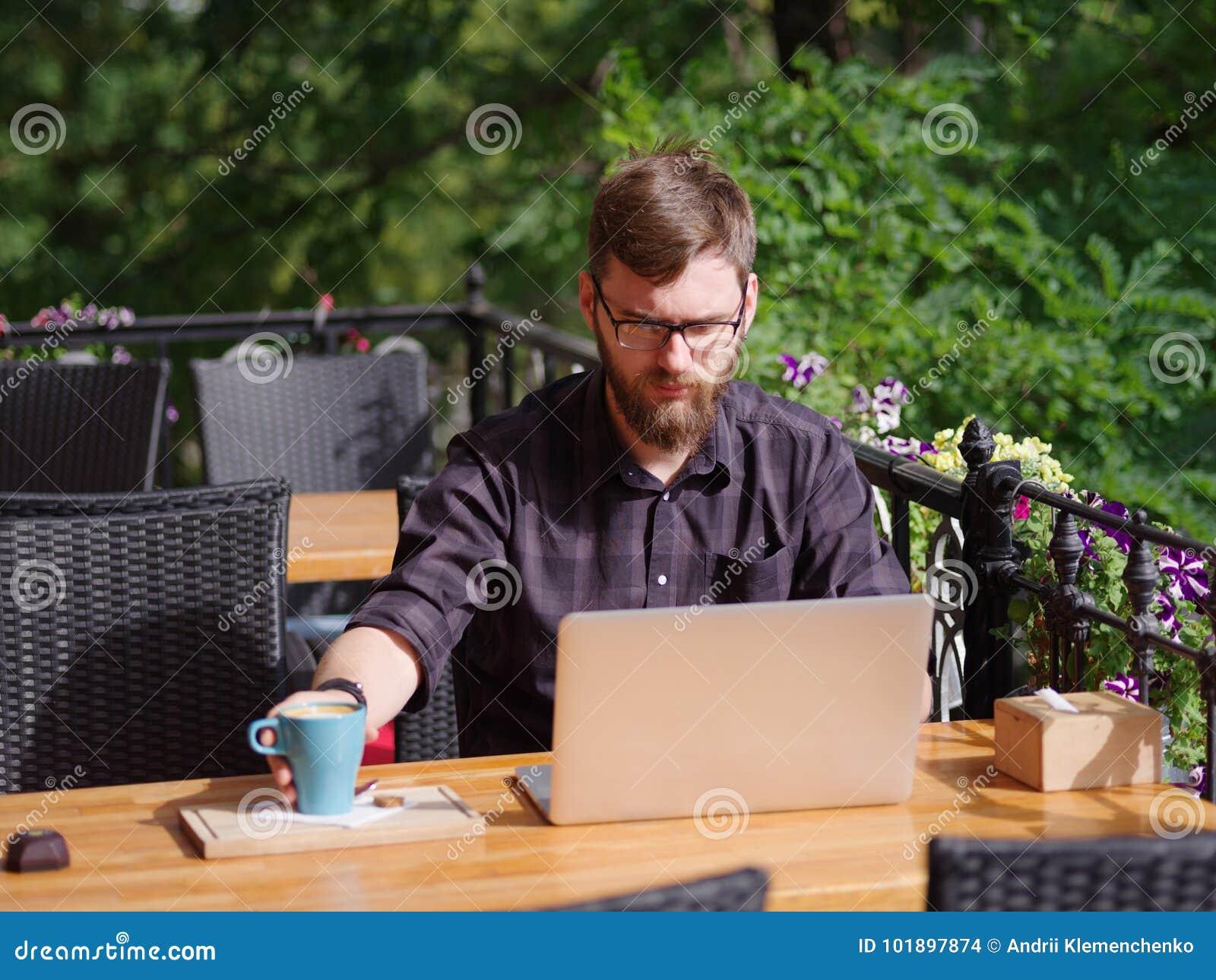 Hombre joven grande que trabaja en el ordenador portátil mientras que se sienta al aire libre Concepto del asunto