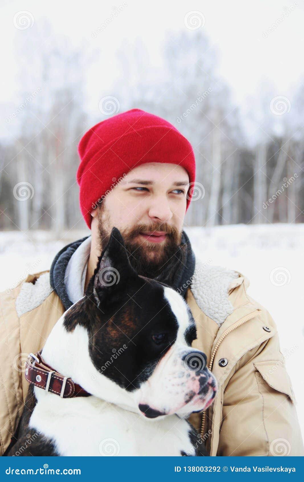 Hombre joven hermoso con su perro del boxeador al aire libre