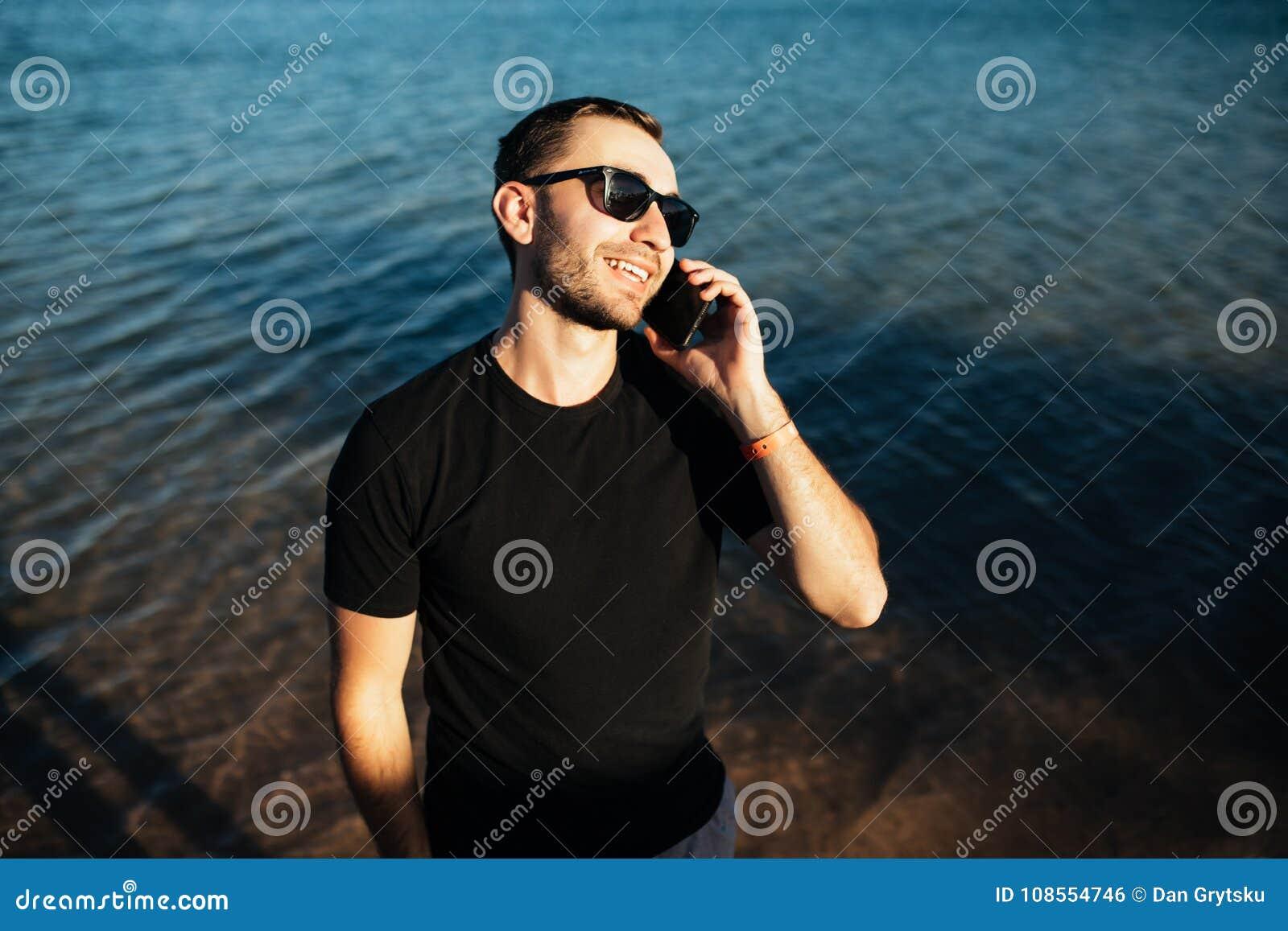 11a3a4058c Hombre joven hermoso en gafas de sol que habla con el teléfono móvil en la  playa
