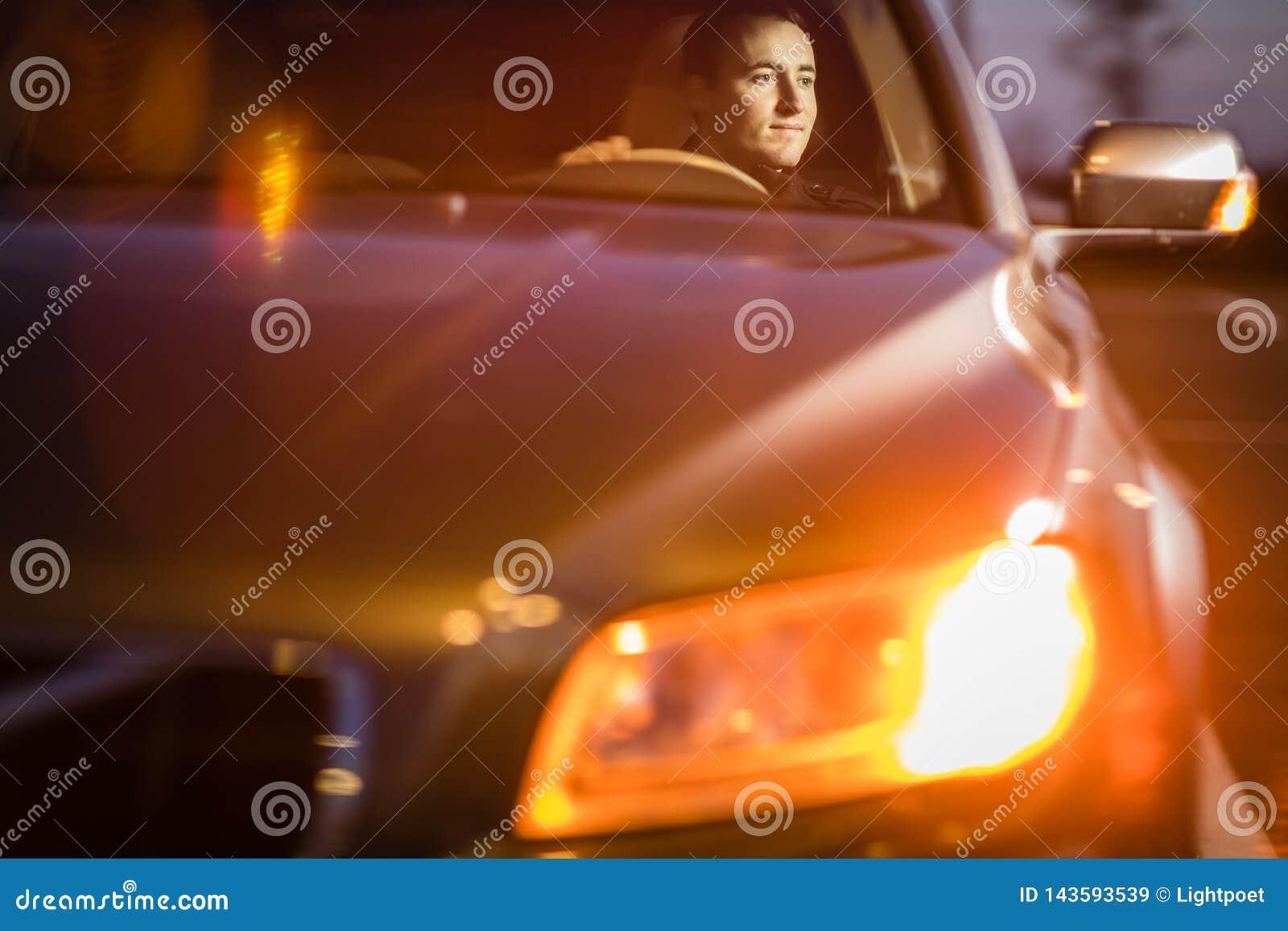 Hombre joven hermoso que conduce su coche en la noche
