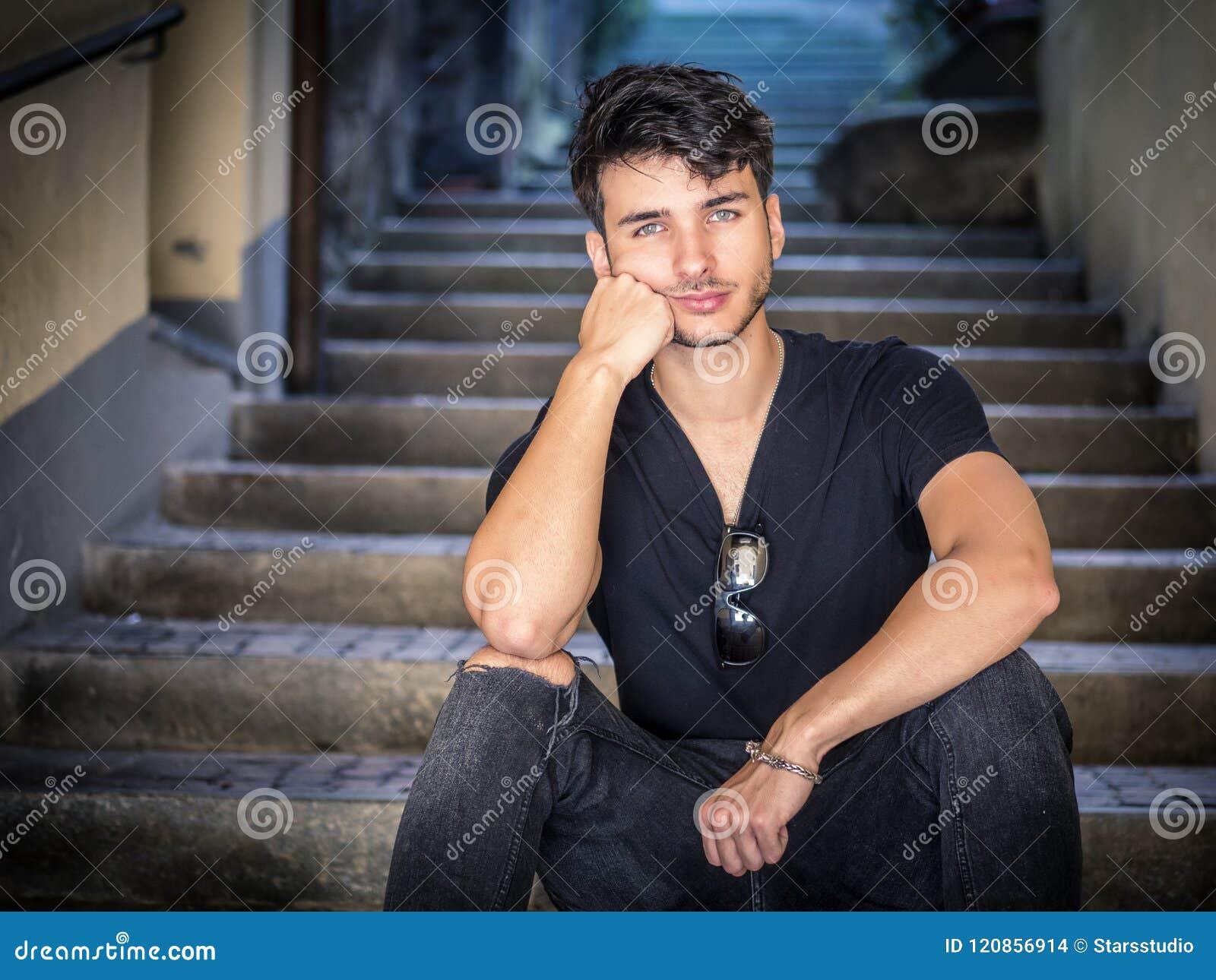 Hombre joven hermoso que se sienta en callejón europeo de la ciudad
