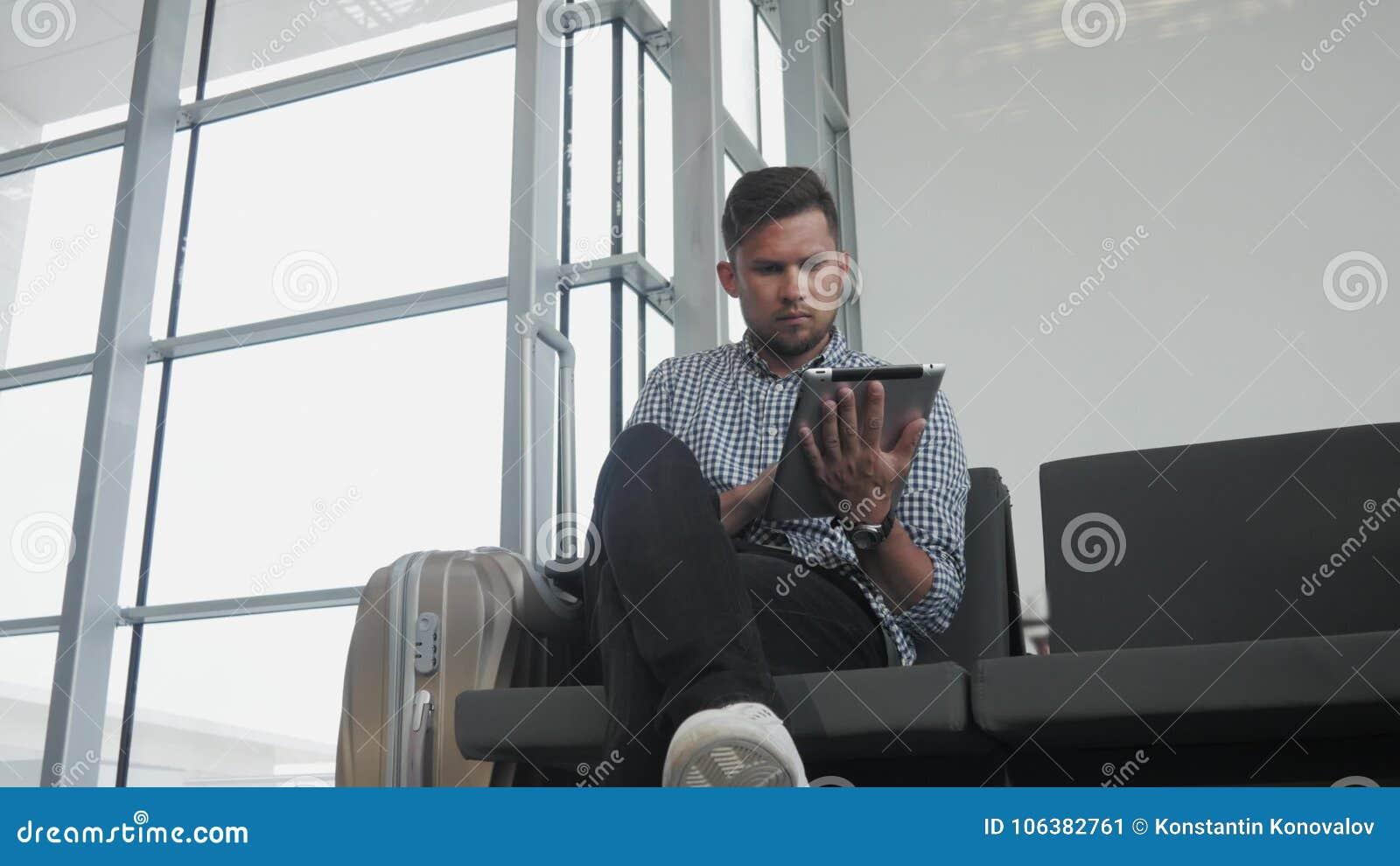 Hombre joven hermoso que sostiene Tablet PC y que trabaja en el aeropuerto, tecnología, concepto que viaja