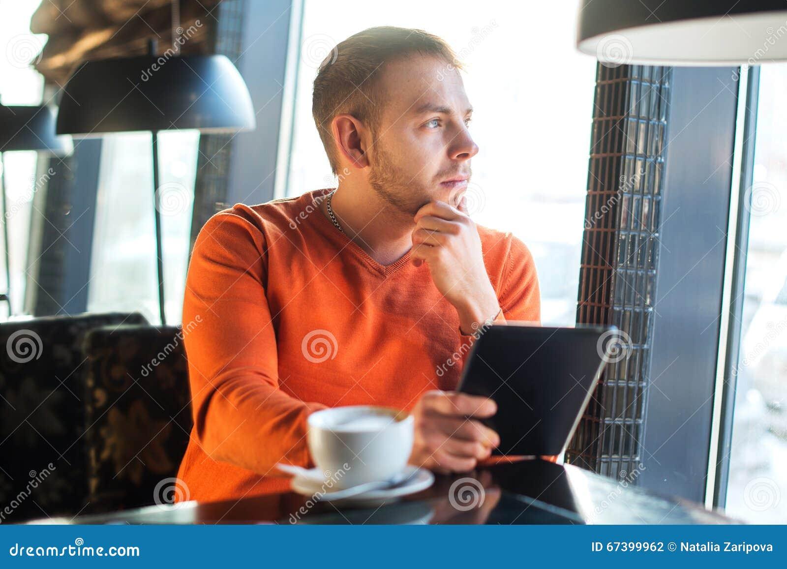 Hombre joven hermoso que trabaja con la tableta, pensamiento, mirando hacia fuera la ventana, mientras que goza del café en café