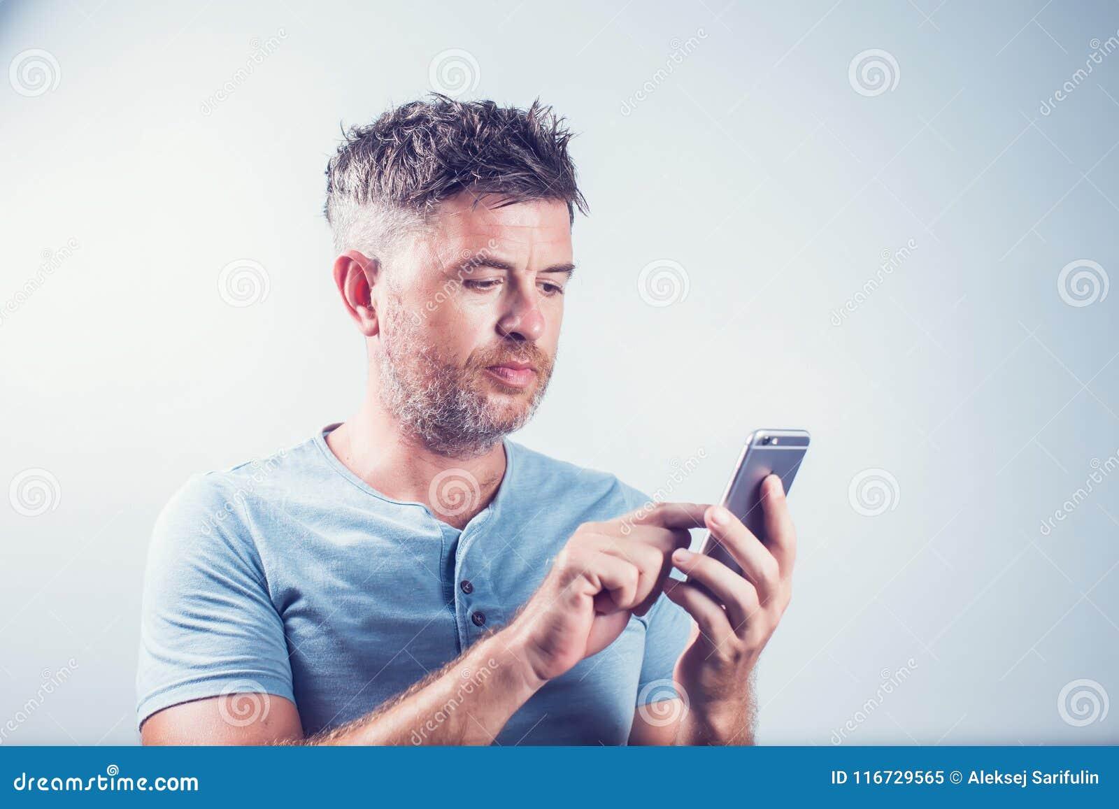 Hombre joven hermoso que usa el teléfono móvil