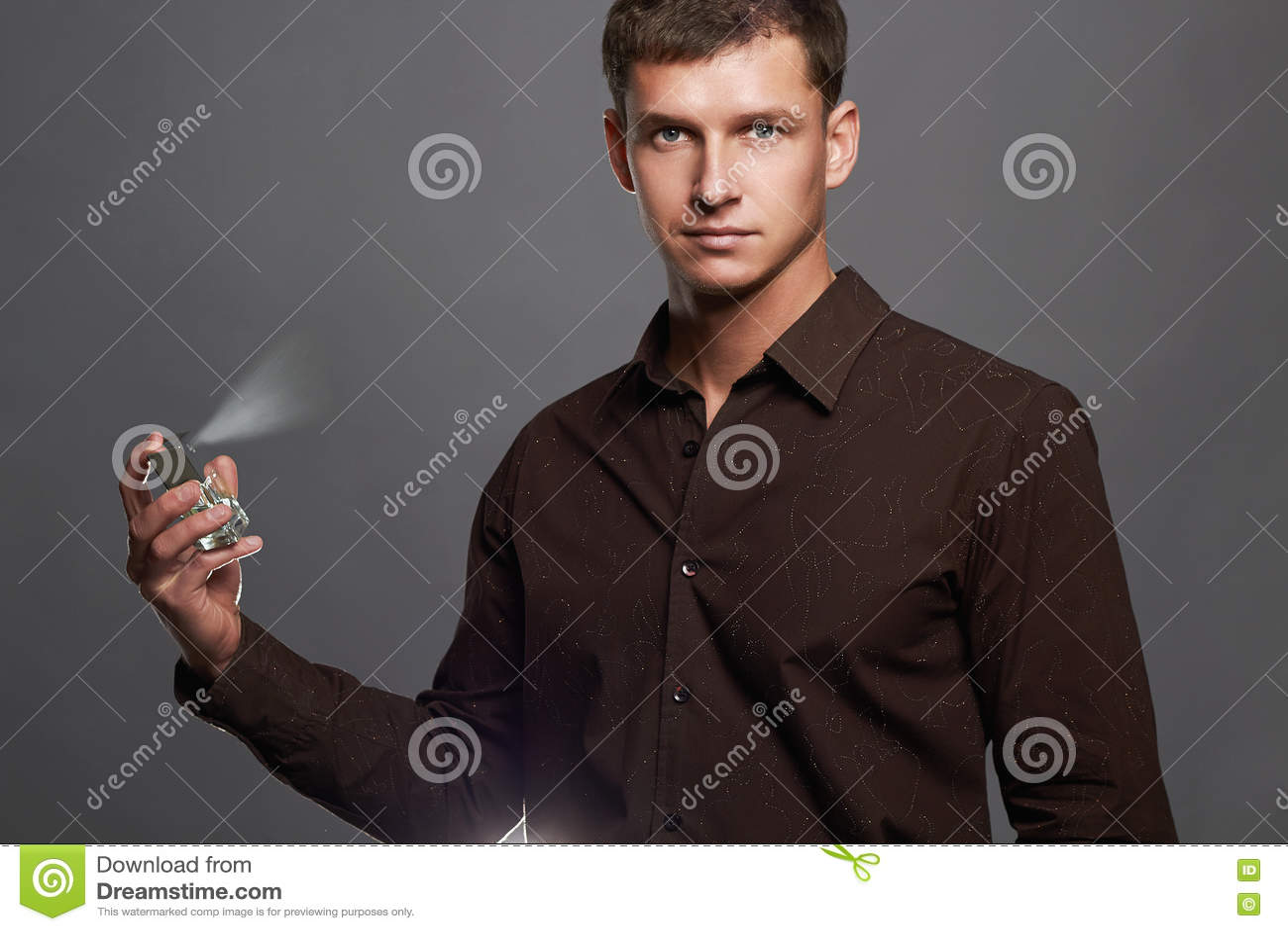 Hombre joven hermoso que usa perfume botella de perfume y fragancia de rociadura