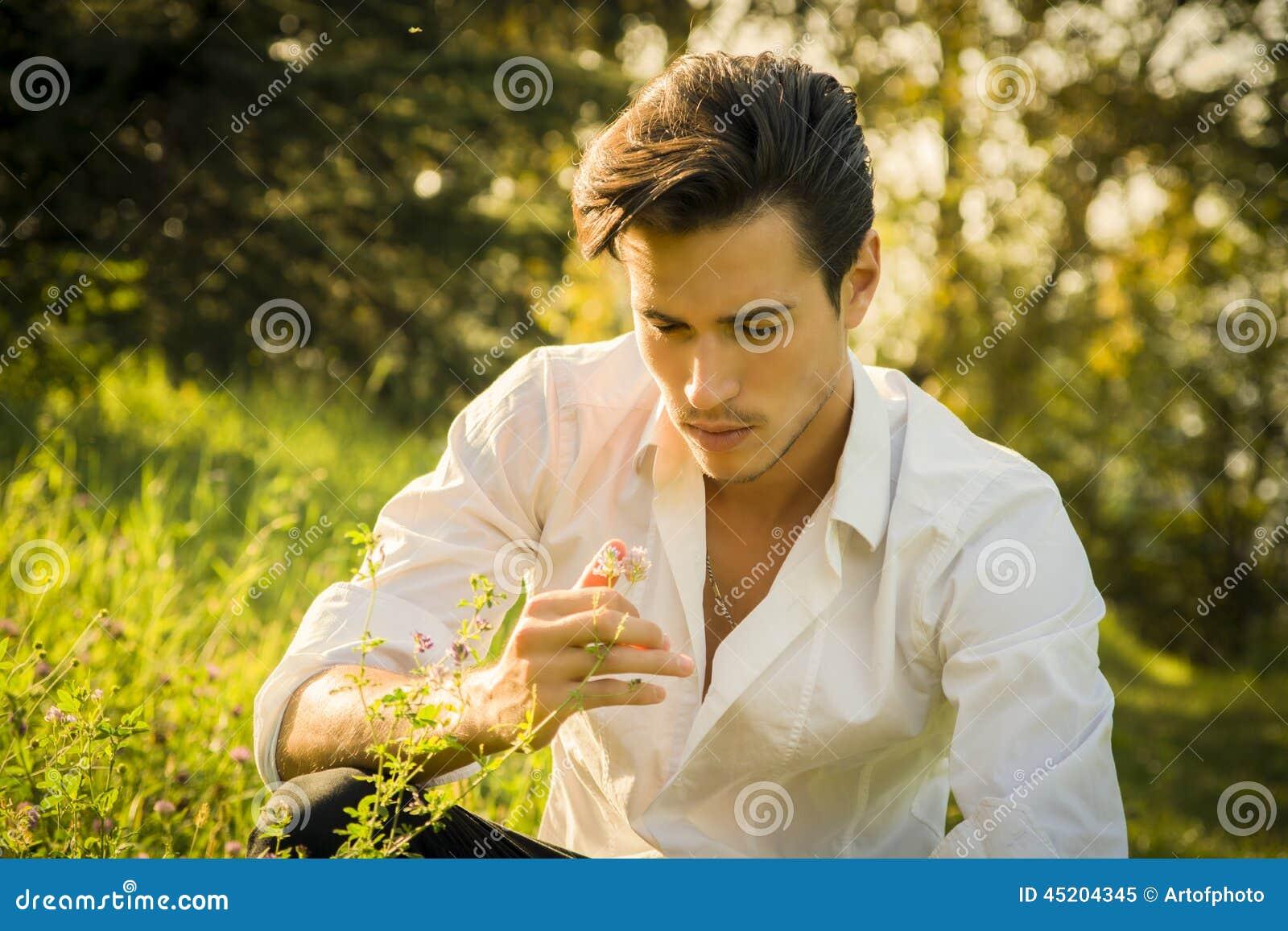 Hombre joven nostálgico que sueña en el parque