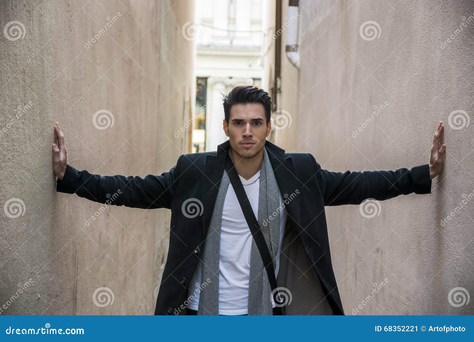 Hombre joven presionado entre dos paredes Opresión, ansiedad