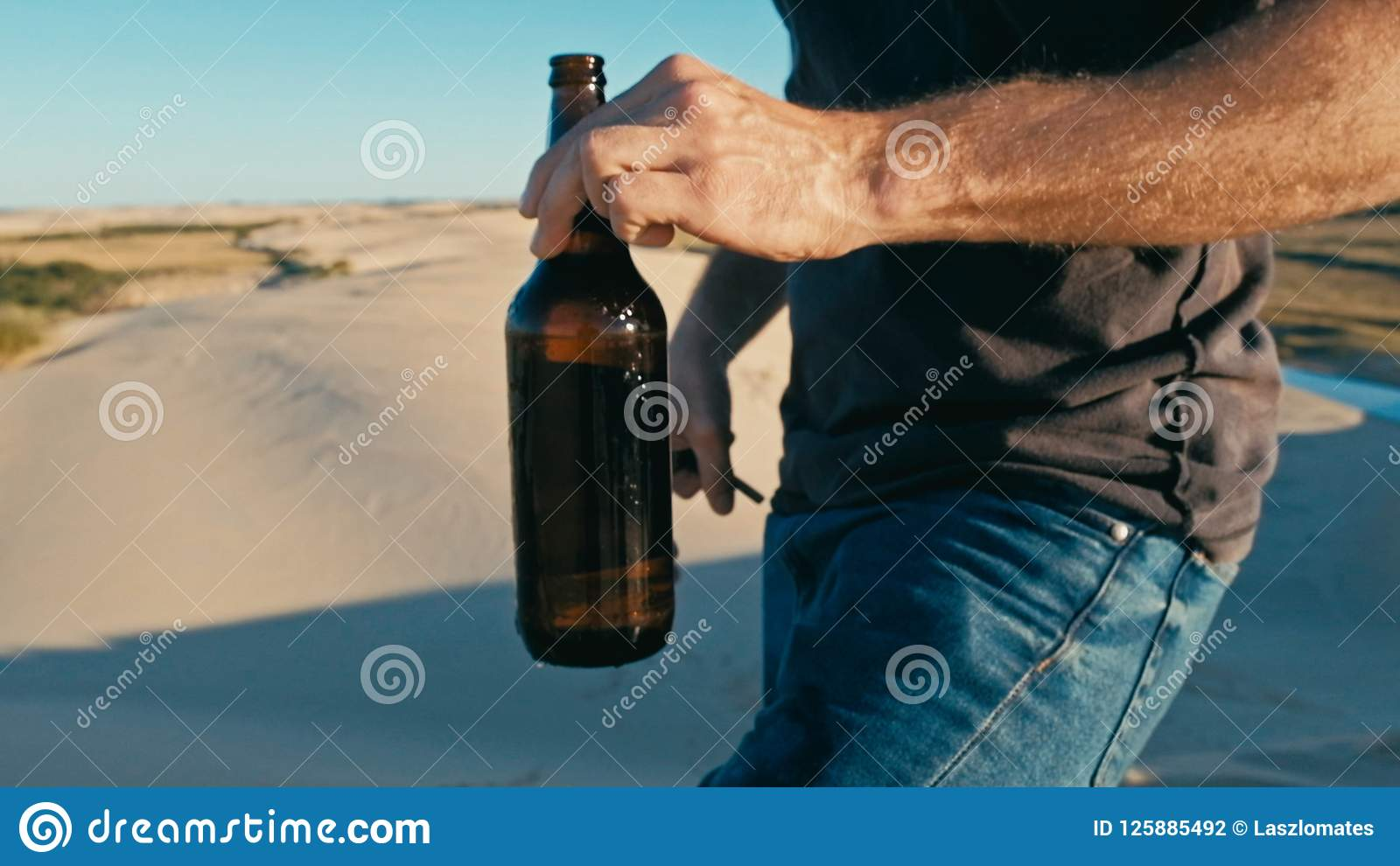 Hombre joven que abre una botella de cerveza al aire libre en las dunas de arena del desierto