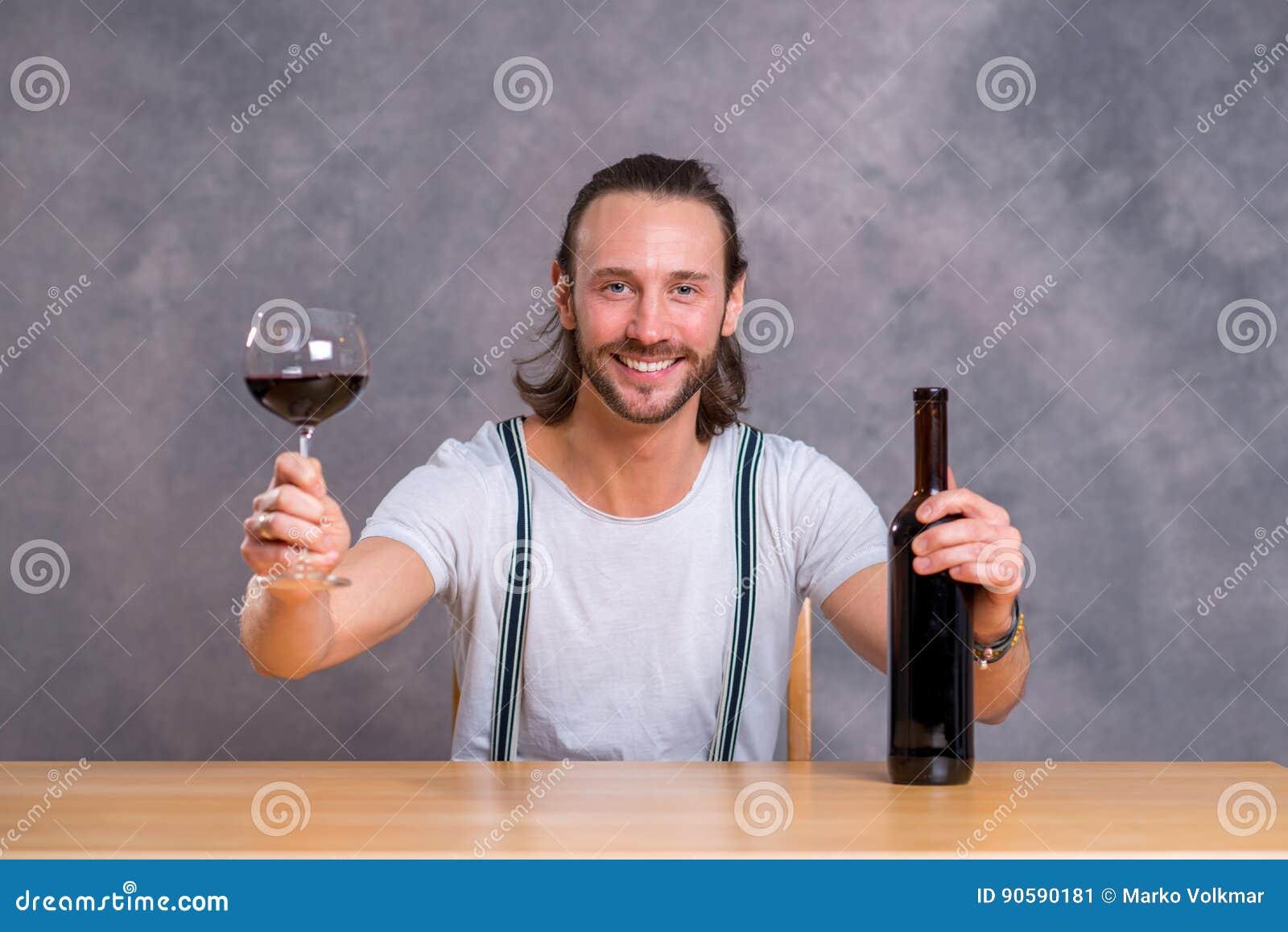 Hombre joven que bebe el vino rojo