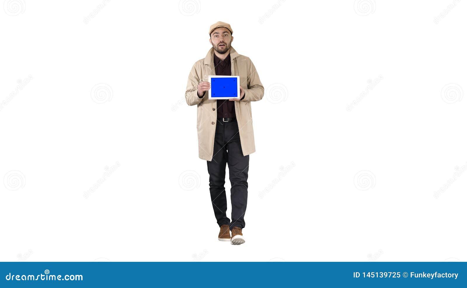Hombre joven que camina, hablando y mostrando la tableta digital con la maqueta de la pantalla azul en el fondo blanco