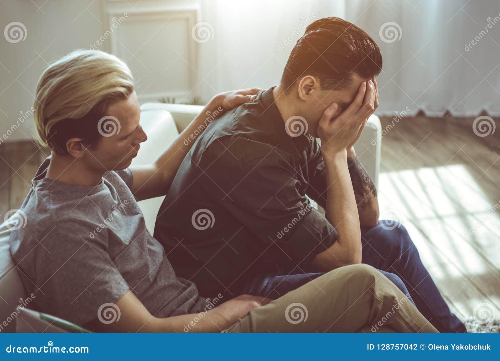 Hombre joven que conforta al novio mientras que él cara de la cubierta con los brazos